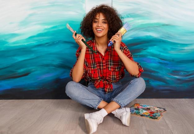 Belle étudiante Mignonne D'origine Africaine Tenant Des Pinceaux Et Posant Sur Ses œuvres Abstraites Sur Toile. Photo gratuit