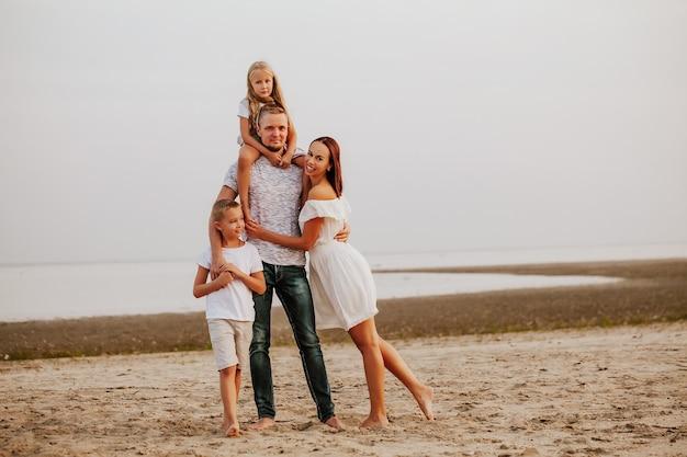 Une Belle Famille Avec Deux Enfants En Vêtements De Couleur Claire Pose Et Sourire Sur La Rive Sablonneuse Photo Premium