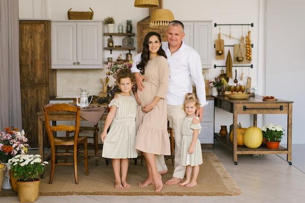 Belle famille avec deux filles souriantes dans la cuisine, maman enceinte tenant les mains sur son ventre Photo Premium