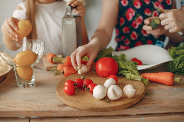 Belle famille prépare des plats dans une cuisine Photo gratuit