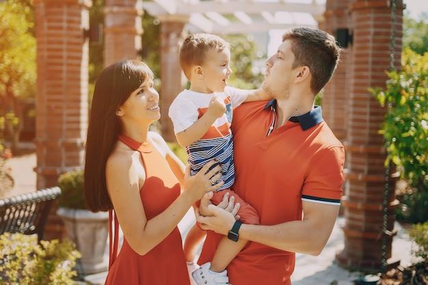 Belle famille en rouge marchant dans la rue et le parc Photo gratuit