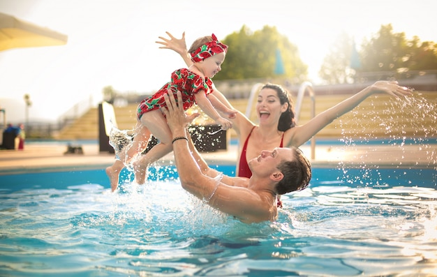 Belle famille s'amuser dans une piscine Photo Premium