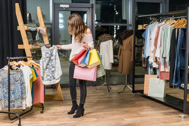Belle femme achète des vêtements en magasin, tenant des sacs dans la main Photo gratuit