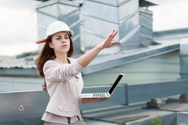Belle femme d'affaires en costume beige, pantalon et casque marron assis sur le toit et tenant un ordinateur portable Photo Premium