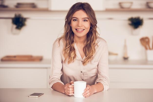 Belle femme d'affaires dans des vêtements décontractés tient une tasse Photo Premium