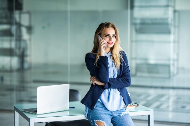 Belle Femme D'affaires Occupée, Debout Au Bureau, écrit Dans Le Planificateur Et Parle Au Téléphone Mobile. Photo gratuit