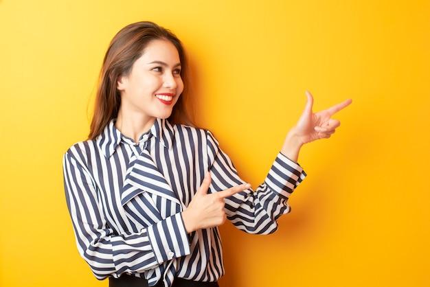Belle femme d'affaires présente quelque chose sur fond jaune Photo Premium