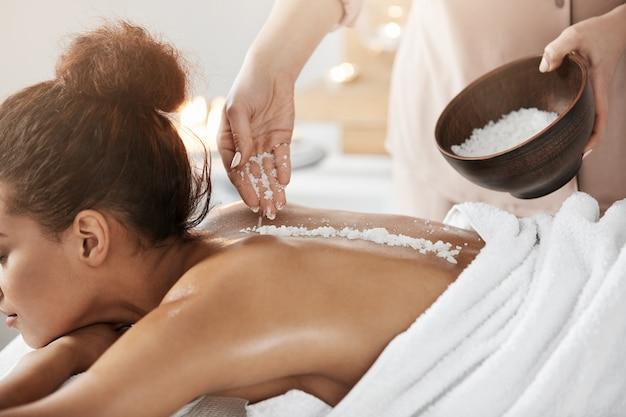 Belle Femme Africaine Relaxante Bénéficiant D'un Massage Santé Spa Avec Du Sel Marin. Photo gratuit