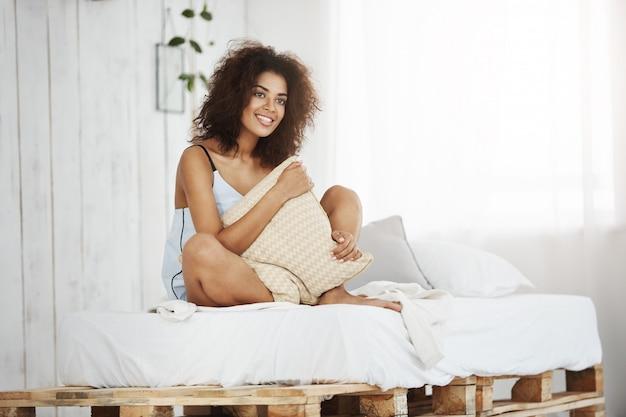 Belle Femme Africaine En Vêtements De Nuit Souriant Tenant Un Oreiller Assis Sur Le Lit à La Maison. Photo gratuit