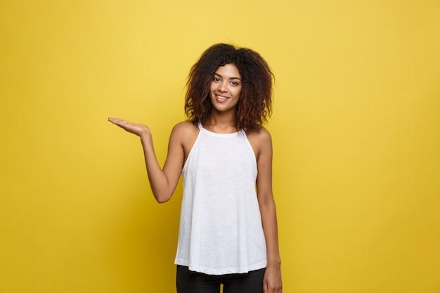 Belle femme afro-américaine attrayante posant jouer avec ses cheveux bouclés d'afro. fond d'écran jaune. espace de copie. Photo gratuit
