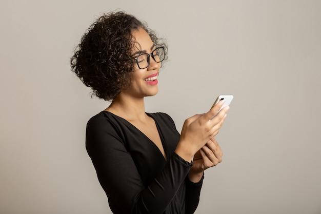 Belle Femme Afro Souriante, Portant Des Lunettes Et Utilisant Un Smartphone Photo Premium