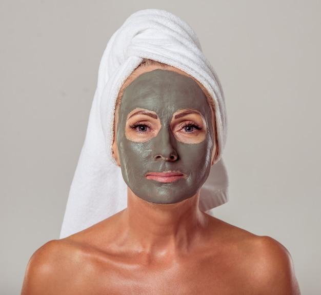 Belle femme d'âge moyen avec un masque d'argile sur son visage. Photo Premium