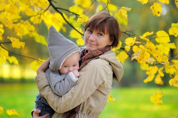 Belle Femme D'âge Moyen Et Son Adorable Petit-fils En Automne Parc Photo Premium