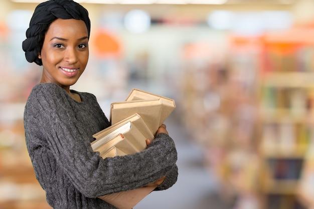 Belle femme américaine afro tenant des livres Photo Premium