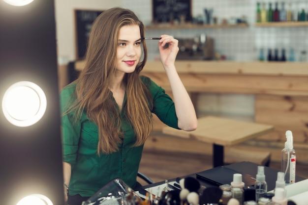 Belle femme appliquant des cosmétiques sur les sourcils Photo gratuit