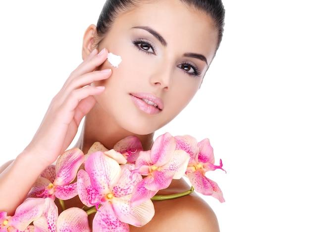Belle Femme Appliquant Une Crème Cosmétique Sur Le Visage Avec Des Fleurs Roses Sur Le Corps - Isolé Sur Blanc Photo gratuit
