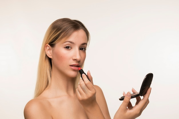 Belle femme appliquant du rouge à lèvres Photo gratuit