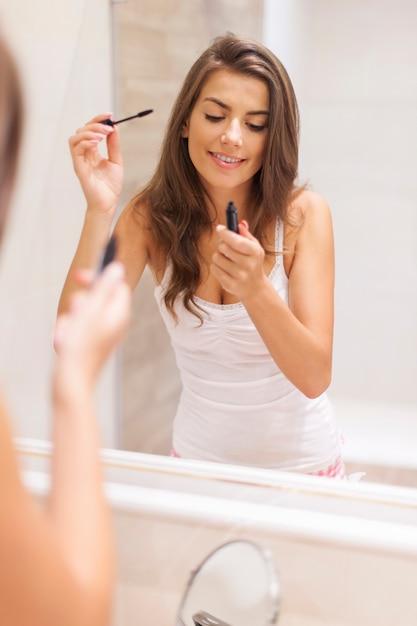 Belle Femme Appliquant Le Mascara Dans La Salle De Bain Photo gratuit