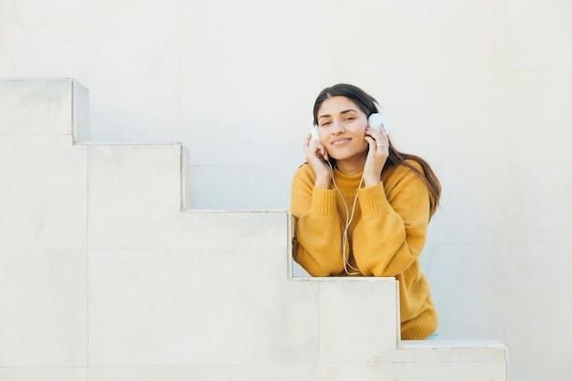Belle femme appréciant l'écoute de la musique sur un casque, regardant la caméra Photo gratuit