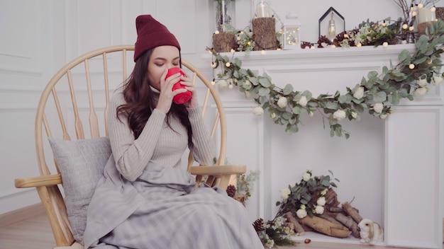 Belle femme asiatique attrayante tenant une tasse de café ou de thé en position couchée sur une chaise Photo gratuit
