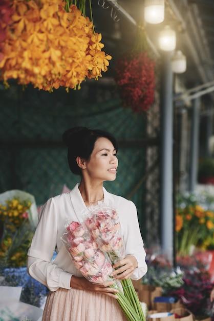 Belle Femme Asiatique Bien Habillée, Posant Avec Des Fleurs Fraîches Au Marché Photo gratuit