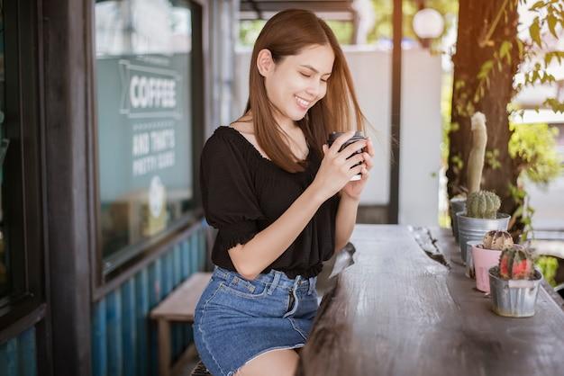 Belle femme asiatique boit du café Photo Premium