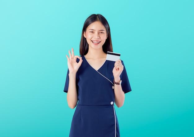 Belle Femme Asiatique Bonne Peau, Montre Signe Ok Avec Robe Et Tenue De Paiement Par Carte De Crédit Sur Fond Bleu. Photo Premium