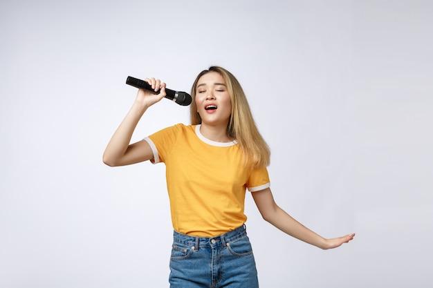 Belle femme asiatique chanter une chanson au micro, studio de portrait sur fond blanc. Photo Premium