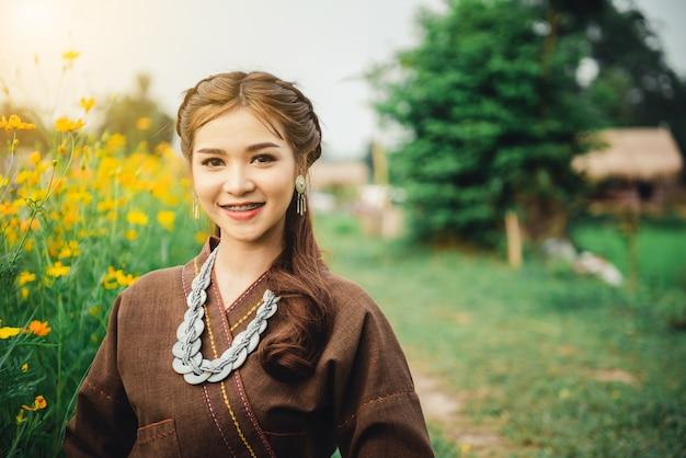 Belle femme asiatique en costume local assis sur le sol et profiter de naturel dans un champ de riz Photo Premium
