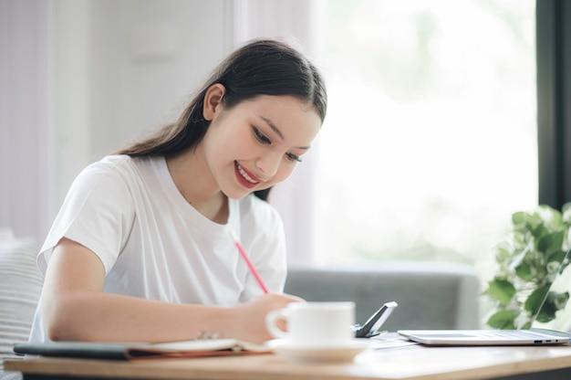 Belle Femme Asiatique écrivant Et Travaillant Assis Dans Le Salon à La Maison. Photo Premium