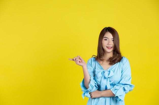 Belle Femme Asiatique Pointant La Main Vers Un Espace Vide De Côté Sur Le Mur Jaune Photo gratuit