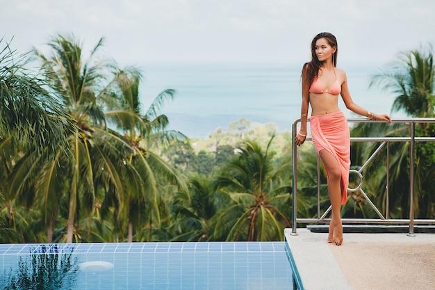 Belle Femme Asiatique Posant En Maillot De Bain Bikini Rose Et Paréo Sur La Terrasse Sur La Villa Tropicale Souriant Heureux En Vacances à Thailnad, Style été Corps Sexy Photo gratuit