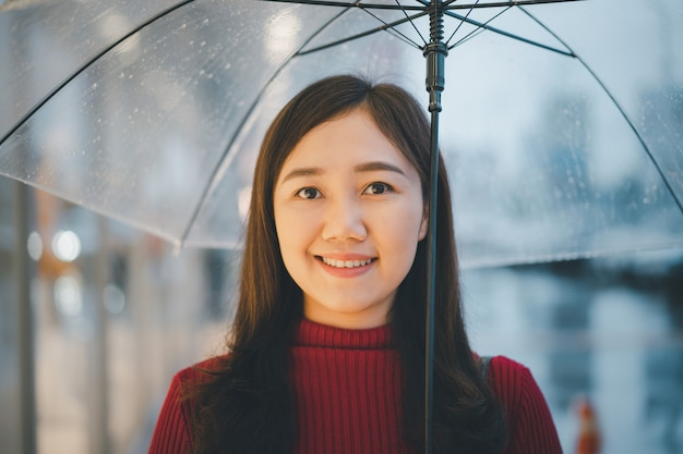 Belle Femme Asiatique En Pull Rouge Debout à Côté De La Route Tout En Pleuvant Et Tenant Un Parapluie Photo Premium