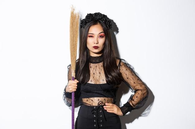 Belle Femme Asiatique En Robe De Dentelle Gothique Et Couronne Noire, Tenant Un Balai Et à La Suspecte Photo gratuit