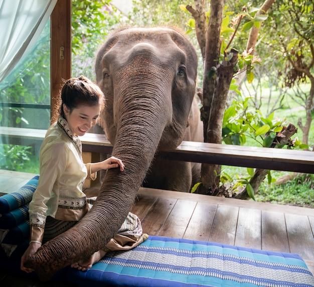 Belle femme asiatique s'asseoir sur un balcon en bois et nourrir l'éléphant. Photo Premium