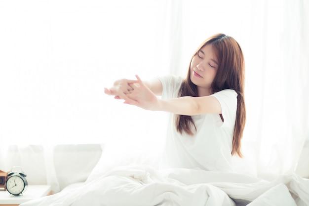 Belle femme asiatique s'étirer et se détendre au lit Photo Premium