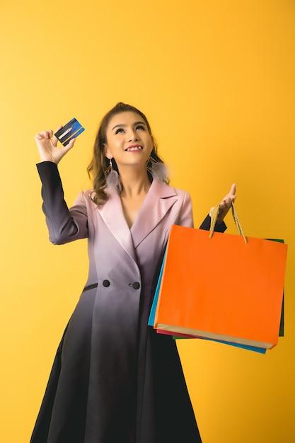 Belle femme asiatique avec sac à provisions et carte de crédit en main Photo gratuit