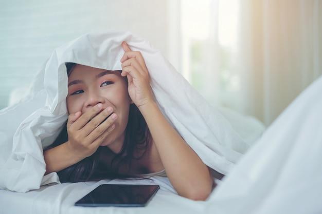 Une belle femme asiatique se détend et travaille avec un ordinateur portable, lisant à la maison. Photo gratuit