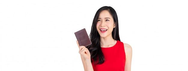 Belle femme asiatique souriante détenant un passeport isolé sur fond de bannière blanche Photo Premium