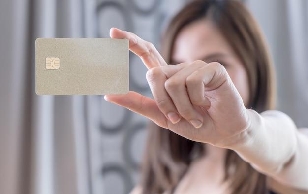 Belle femme asiatique tenant une carte de crédit vierge doré Photo Premium