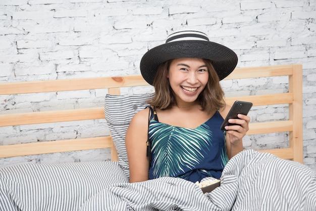 Belle femme asiatique toucher tablette smartphone et manger du pop-corn sur lit Photo Premium