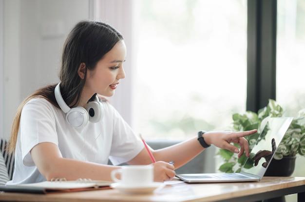 Belle Femme Asiatique Travaillant Avec Ordinateur Portable Calcul Tout En étant Assis Dans Le Salon à La Maison. Photo Premium