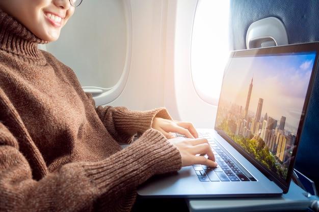 Belle femme asiatique travaille avec un ordinateur portable en avion Photo Premium
