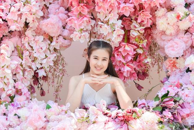 Belle Femme Asiatique Vêtue D'une Robe Blanche Assise Avec Une Belle Fleur Rose. Photo Premium