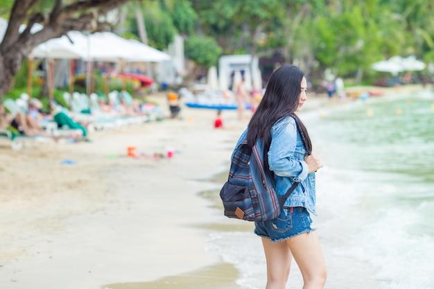 Belle Femme Asiatique Voyageur Avec Un Sac à Dos Debout Sur La Plage. Photo Premium