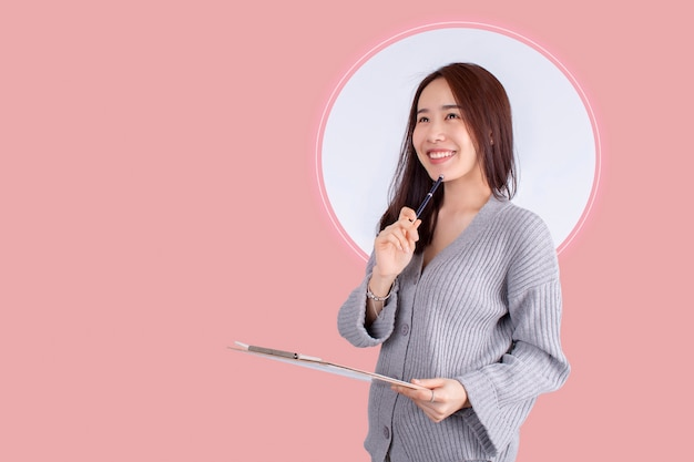 Belle femme d'asie pensant debout isolé sur fond rose Photo Premium