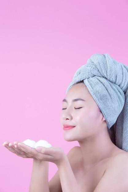 Belle femme en asie se lave le visage sur fond rose. Photo gratuit