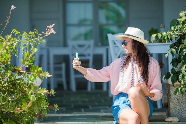 Belle femme assise au café de plage en plein air Photo Premium