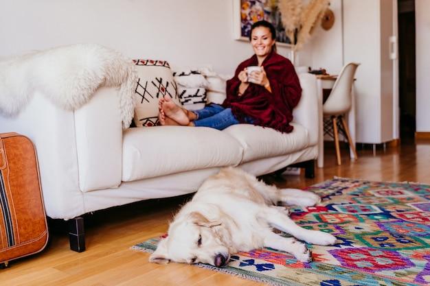 Belle Femme Assise Sur Le Canapé, Appréciant Une Tasse De Thé. Chien Mignon De Golden Retriever En Plus. Mode De Vie à L'intérieur. Vue De Dessus Photo Premium