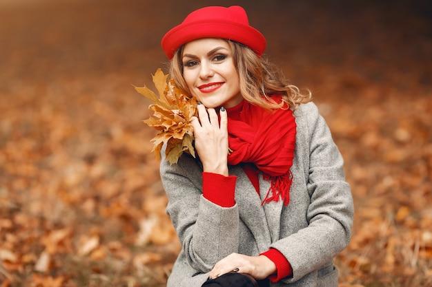 Belle femme assise dans un parc en automne Photo gratuit